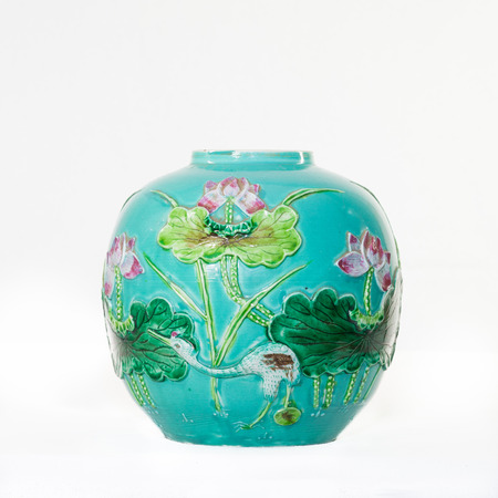 water bird: Antique turquoise blue tin-glazed Majolica vase with a bird and water lilies in raised relief  isolated on a white background
