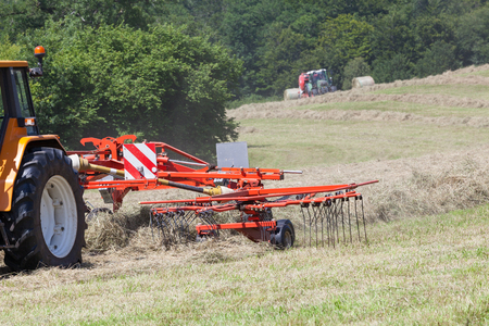 tines: Farmer using a rotary rake to turn dry grass for hay and fodder for livestock with some motion blur to the tines. Baler baling the crop in the background.