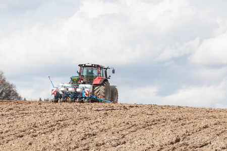harrowing: Agricultural drill or planter on a hilltop skyline with ploughed earth foreground texture as the farmer plants the spring crop of maize , sea mays Stock Photo