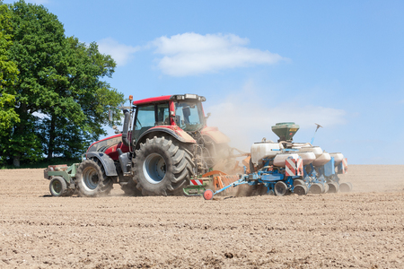 seed drill: Farmer planting the spring crop with an agricultural planter and harrow in a fallow field on the skyiline