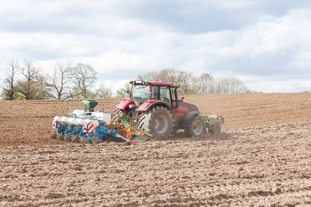 seeding: Farmer planting and seeding the spring crop with a five row agricultural planter in a newly ploughed , or plowed, field