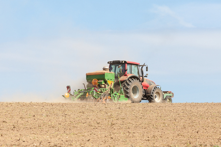 seed drill: Farmer planting crops with an agricultural  planter with a large hopper in summer, skyline view