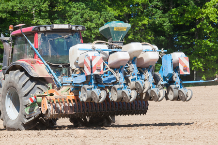seed drill: Detail of an agricultural planter raised in the air as the farmer turns the tractor at the end of a run across a field planting  the spring crop