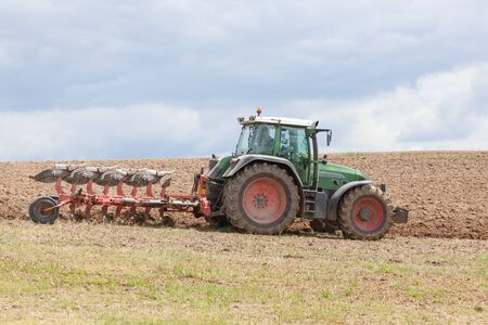plough: Farmer ploughing, or plowing, an overwintered fallow field with a tractor and plough, or plow, to plant the spring crop, close up side view