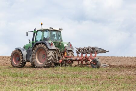ploughing field: Farmer ploughing  an overwintered fallow field for planting the spring crop  with a plough and tractor in a close up skyline view