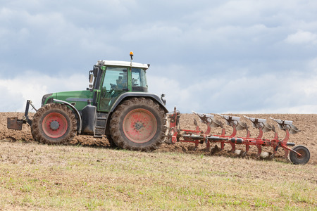 ploughing field: Farmer ploughing a fallow field preparing the soil for planting the spring crop, close up side view
