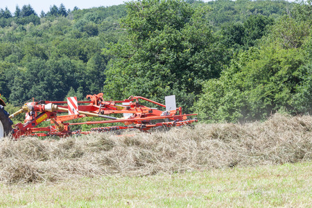 mechanization: Rotary hay rake turning drying pasture grass for baling for hay and winter feed for livestock, close up view of the rake raking the grass