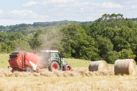 baler: Farmer baling dried grass for hay with a tractor and baler, two round hay bales at the side in a rural hilltop pasture Stock Photo