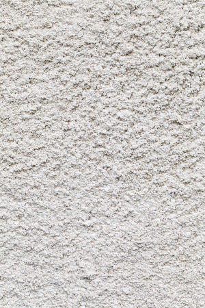 gritty: White roughcast lime mortar plaster wall background texture with a rough gritty crepi  finish on an old historic building made from a mixture of lime and coarse sand in the old tradition in a full frame view Stock Photo