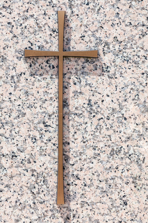 memorial cross: A simple gold memorial cross on a polished light pink granite slab with  copy space for a tribute to a departed loved one, gravestone or funeral concept