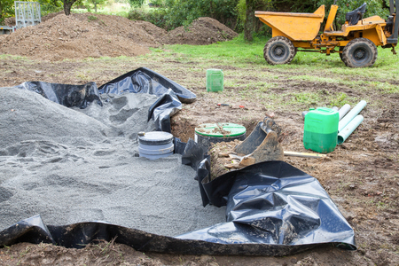 anaerobic: Installing the sand filter on a septic tank showing the liner , sand, filter and pump before pouringthe gravel with a small front end loader in the background Stock Photo