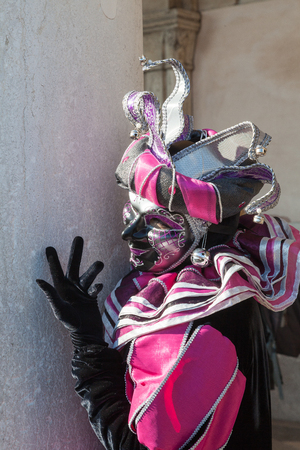Feb 2017 Venice Carnival, Italy. Anonymous person in pink and black joker costume peering round a stone pillar on the Doges Palace with copy space in a close up view