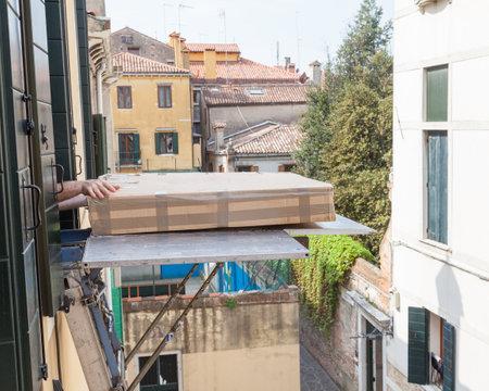 La entrega de muebles a un segundo piso utilizando un montacargas o ascensor durante las mudanzas con un gran cartón caja de cuadros al nivel de la ventana y las manos se extienden a través de sacarlo de la plataforma. Foto de archivo - 80069253