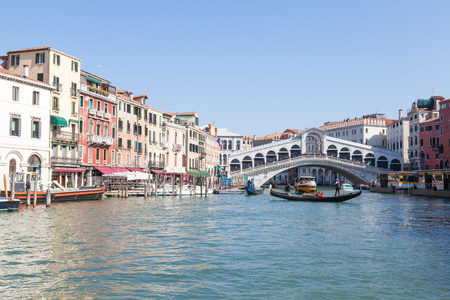 View of Rialto Bridge , Venice, veneto,  Italy from the Grand Canal with a gondola passing in front of it and reflections on the water from the historic palazzos on a sunny blue sky day in a travel and tourism concept.