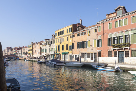 Fondamenta dei Ormisini, Cannaregio, Venice, Italy in evening light with moored boats in the canal and locals drinking at taverns  in front of colorful buildings Stock Photo - 89465221