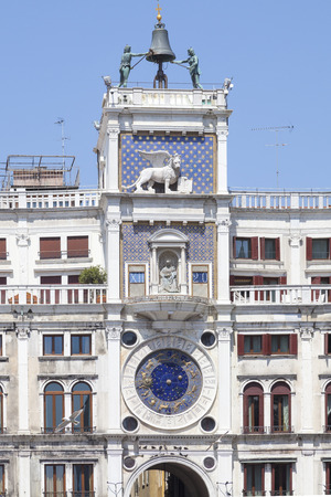 winged lion: Detail of the top of the medieval Bell Tower in Piazza San Marco, Venice, Italy  with its striking figures on the  historic bronze bell and astronomical clock , Two seagulls flying in th e foreground. Foto de archivo