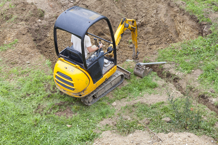 Workman using a mini digger to excavate  a hole for a swimming pool in a garden lawn with green grass viewes from above.