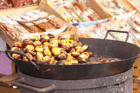 Autumn chestnuts, Castanea,  roasting over an old charcoal burner on a street stall in a low angle close up view with copy space