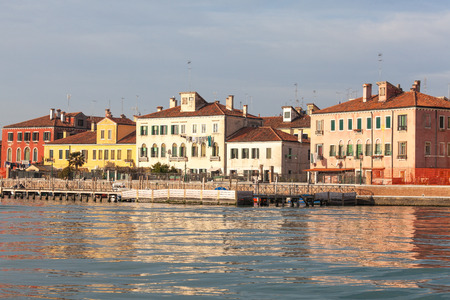 Colorful houses on the island of San Pietro di Castello at dusk, Venice, Italy with reflections on the lagoon