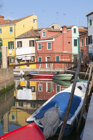 Reflections of colourful houses in Burano, Venice, Veneto, Italy in a canal with wooden bridge.