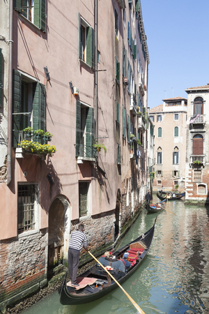 Gondolas with tourists sightseeing on a scenic back canal Cannaregio, Venice, Veneto, Italy
