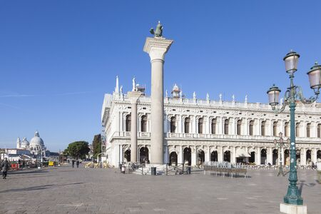 Biblioteca Nazionale Marciana and the columns in Piazetta San Marco, Venice, Italy early morning with view along Riva Schiavonni to Basilica  Santa Maria della Salute
