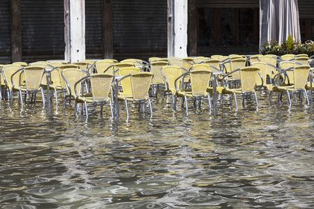 Acqua Alta or tidal High Water in Piazza San Marco, Venice, Italy with restaurant chairs outdoors in the water in front of shuttered shops