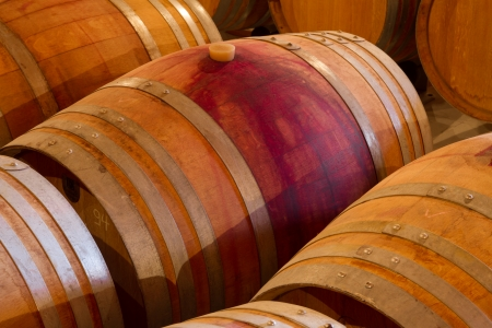 Selected wine varieties go through the aging process in oak wine barrels  in a winery cellar on Crete  photo