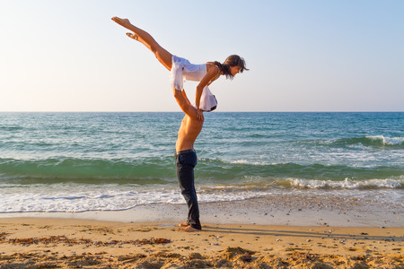 Summer afternoon at a sandy beach with the ocean in the background, a young couple practices a dance scene   photo