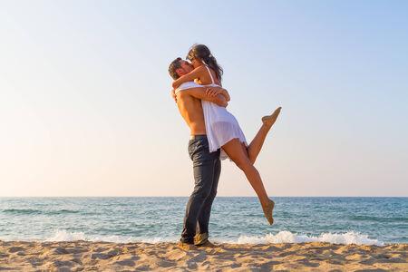 pareja besandose: Joven pareja bes�ndose en la playa en la tarde Foto de archivo