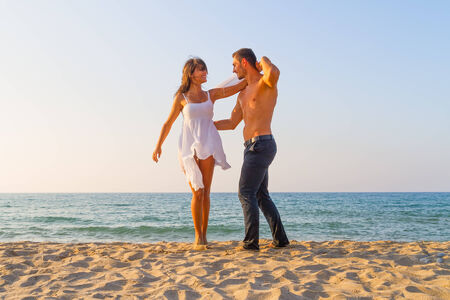 Young couple love play  at the beach in late afternoon photo
