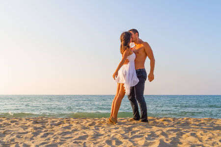 Young couple kissing at the beach in late afternoon photo