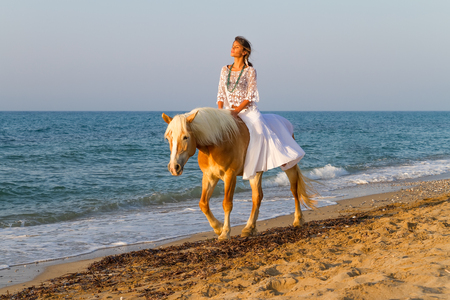 White dressed attractive young girl enjoys a romantic horse ride along a sandy shoreline in late afternoon mid summer sun   photo