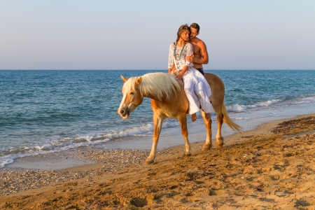 Attractive young couple enjoys a romantic horse ride along a sandy shoreline in late afternoon mid summer sun   photo