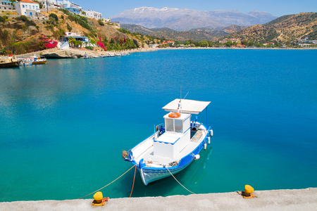 Small blue and white fishing boat moored at Aghia Galinis fishing port south of Crete. photo