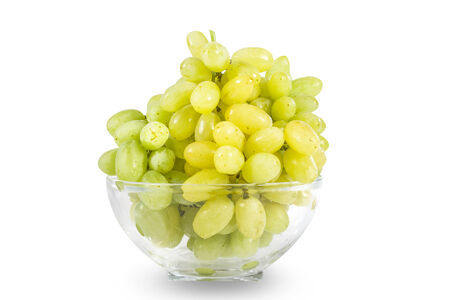 Glass bowl of delicious ripe fresh whole and sliced white grapes isolated on white photo