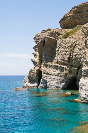 Soft steep pebble rock cliffs towering over the turquoise waters at the south coast of Crete. Stock Photo