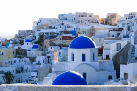 Located in the Aegean Sea, the Greek volcanic island of Santorini,  part of the Cyclades islands, is known as a top vacation destination. It is famous for its  blue domed churches, the majestic sunset, the steep cliffs, and the uniquel architecture. photo