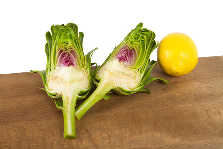 Whole and sliced fresh delicious uncooked artichokes isolated on white background  photo