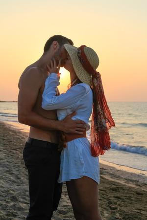 代、優しく抱きしめると、ちょうど日没前にビーチでキスで幸せな若いカップル。