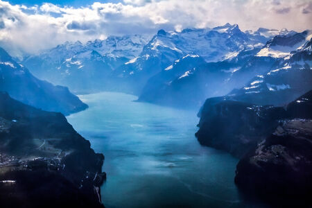 icecaps: Unique and magnificent airplane aerial view of central snow-capped Swiss Alps, lakes, and blue skies patched with dramatic high cloud formations. Stock Photo