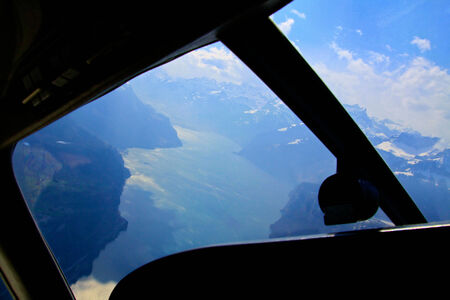 icecaps: Unique and magnificent airplane aerial view of central snow-capped Swiss Alps, lakes, and blue skies patched with dramatic high cloud formations