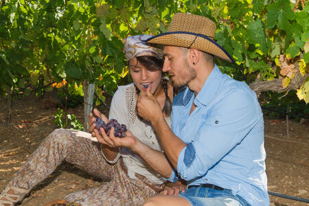 growers: Young couple, vine growers, enjoy eating grapes while seated on the ground under the vines.
