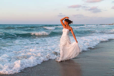 wet dress: Barefoot young bride in a partially wet  wedding dress, enjoys walking in the water on a sandy beach in late summer, at dusk.