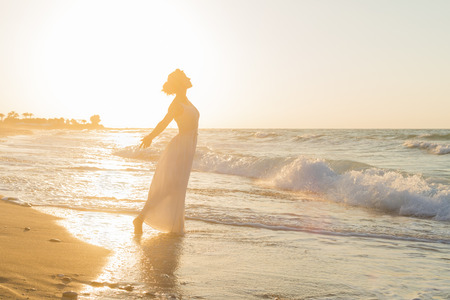 lonesome: Barefoot young woman in a long white dress enjoys a lonesome walk on a sandy beach in a late summer hazy day, at dusk.