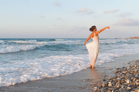 wet dress: Barefoot young woman in a long white partially wet dress, enjoys a lonesome walk in the water, on a sandy beach in a late summer day, at dusk. Stock Photo