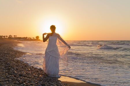 lonesome: Barefoot young bride in a white wedding dress enjoys a lonesome walk on a wet sandy beach in a late summer hazy day, at dusk. Stock Photo