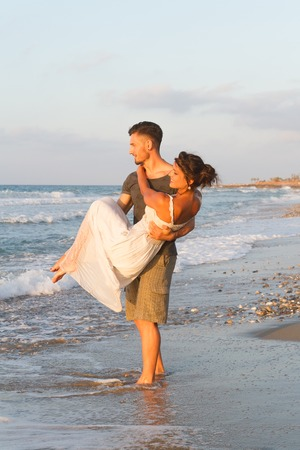 getting late: Loving young couple at the beach , in a late summer hazy day at dusk, wearing  a white dress and shorts, enjoying, going barefoot in the ocean water, getting wet, teasing and kissing one another. Stock Photo