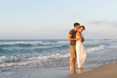 wet dress: Loving young couple at the beach , in a late summer hazy day at dusk, wearing  a white dress and shorts, enjoying, going barefoot in the ocean water, getting wet, teasing and kissing one another. Stock Photo
