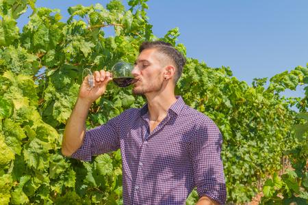 joven agricultor: Joven agricultor sabe un vaso de vino tinto en el vi�edo.